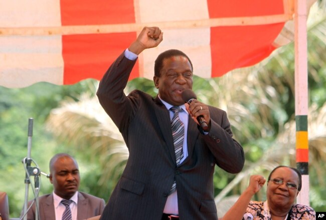 FILE - Then-Zimbabwean Vice President Emmerson Mnangagwa greets party supporters at the ZANU-PF headquarters in Harare, Zimbabwe, Feb, 10, 2016. Mnangagwa's firing by Mugabe precipated the current political crisis in Zimbabwe.
