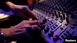 FILE - An audio engineer is seen at the controls of a sound mixer during a recording session. An boost in music sales in 2015 to $15 billion is due mostly to an increase in streaming subscriptions, which overtook physical sales for the first time.
