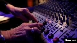 Seorang teknisi audio mengontrol suara dalam sebuah proses rekaman di studio.