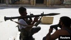 ພວກນັກລົບຂອງກຸ່ມກອງທັບຊີເຣຍເສລີພວມລໍຖ້າຍິງຈະຫຼວດໝາກປີ ໃສ່ລົດຖັງທະຫານຊີເຣຍທີ່ຄຸ້ມ Salaheddine ໃນເມືອງ Aleppo (10 ສິງຫາ 2012)
