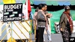 泰國反政府示威者站在抗議標語前。