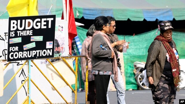 Thai anti-government protesters chat next to a protesting banner outside a makeshift camp where their colleagues were shot outside the Prime Minister's office of Government House, Saturday, Dec. 28, 2013 in Bangkok, Thailand.