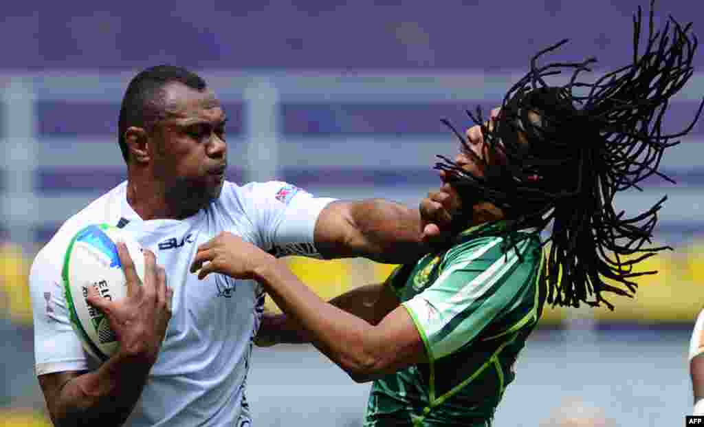 South Africa's Cecil Afrika (R) is hit by Fiji's Vereniki Goneva (L) during the quarter final match at the 2013 Rugby World Cup Sevens Championships in Moscow, Russia.