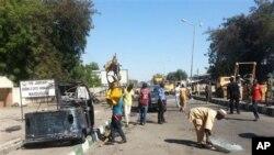 Petugas penyelamat membersihkan jalan menyusul bom mobil bunuh diri di sebuah pos militer di Maiduguri, Nigeria (14/1). (AP/Jossy Ola)