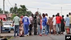 Des habitants auprès de cadavres retrouvés dans les rues de Bujumbura, samedi 12 décembre 2015. (AP Photo)