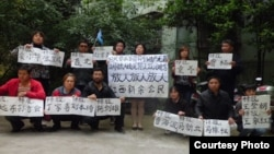 劉萍(站立者左一)等新余市公民舉牌聲援被捕北京活動人士。(圖片來源:維權網)