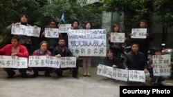 Bà Lưu Bình, ông Ngụy Trung Bình và ông Lý Tư Hoa cùng các nhà hoạt động khác đứng trước một tòa chung cư, căng biểu ngữ đòi các quan chức chính phủ kê khai tài sản. Một tuần sau đó họ đã bị bắt.