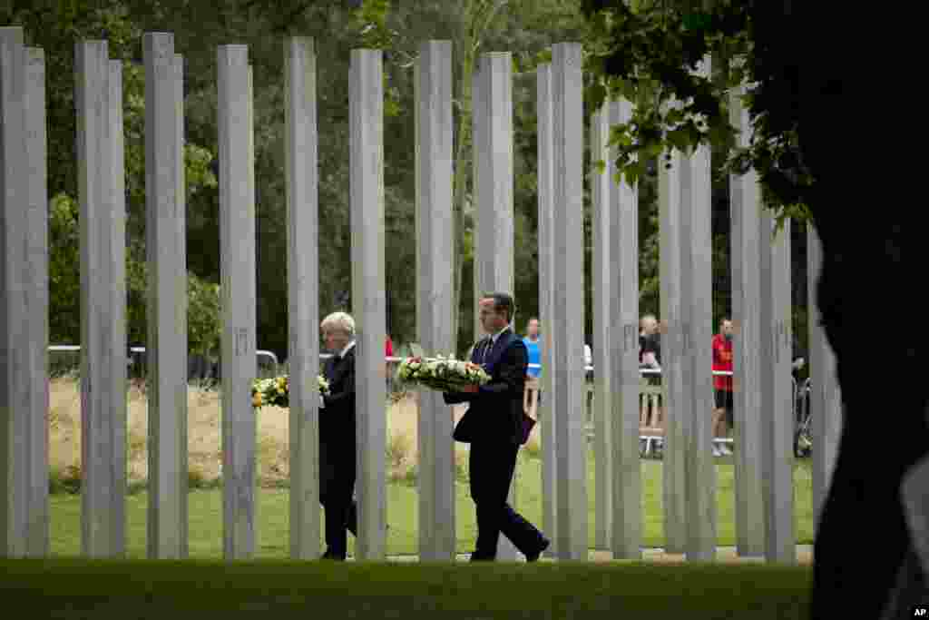 Britain's Prime Minister David Cameron, right, and London Mayor Boris Johnson walk through the 7/7 memorial in Hyde Park, London, to lay wreaths to mark the 10th anniversary of the suicide bomb attacks on London's transit system.