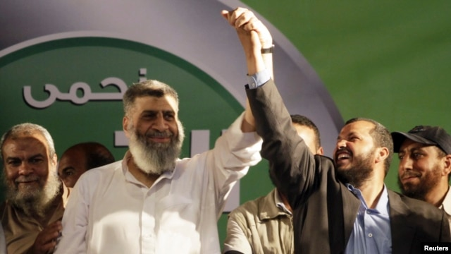 FILE - Leading member of the Islamic Jama'a Assem Abdel Maged (L) gestures with other leaders during a protest around the Raba El-Adwyia mosque square in the suburb of Nasr City, Cairo, June 28, 2013.