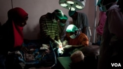 Surgeons-in-training close an incision in a new operating theater, Ras Kamboni, Somalia, July 6, 2012. (VOA - R. Gogineni)