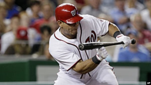 Washington Nationals' Wilson Ramos hitting a sacrifice bunt to drive in teammate Michael Morse for the go-ahead run in the seventh inning against the Chicago Cubs at Nationals Park in Washington, July 6, 2011.