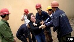 Bà Huang Sufang cố gắng ngăn căn nhà của mình khỏi bị phá hủy trong một ngôi làng ở tỉnh Quảng Đông, phía nam Trung Quốc