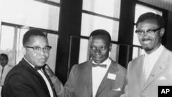 Joseph Kasavubu, à gauche, chef du parti Abako, et Patrice Lumumba, chef du Mouvement national du Congo (MNC), serrent la main dans le hall du Parlement du Congo à Léopoldville, le 20 juin 1960.