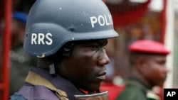 FILE - A police officer stand guards during a demonstration in Lagos, Nigeria, May. 1, 2014. An elite Nigerian police squad set up to combat violent crime is torturing detainees to extract lucrative bribes and confessions, an new Amnesty International rep