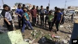 Grupa Iračana okupljena na mestu eksplozije u Baviji, istočnoj četvrti Bagdada