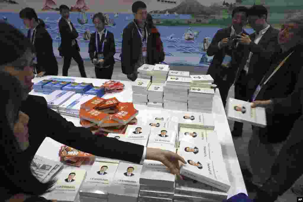 Attendees pick up copies of a book on the governance of Chinese President Xi Jinping at the media center for the Second Belt and Road Forum, In Beijing, China.