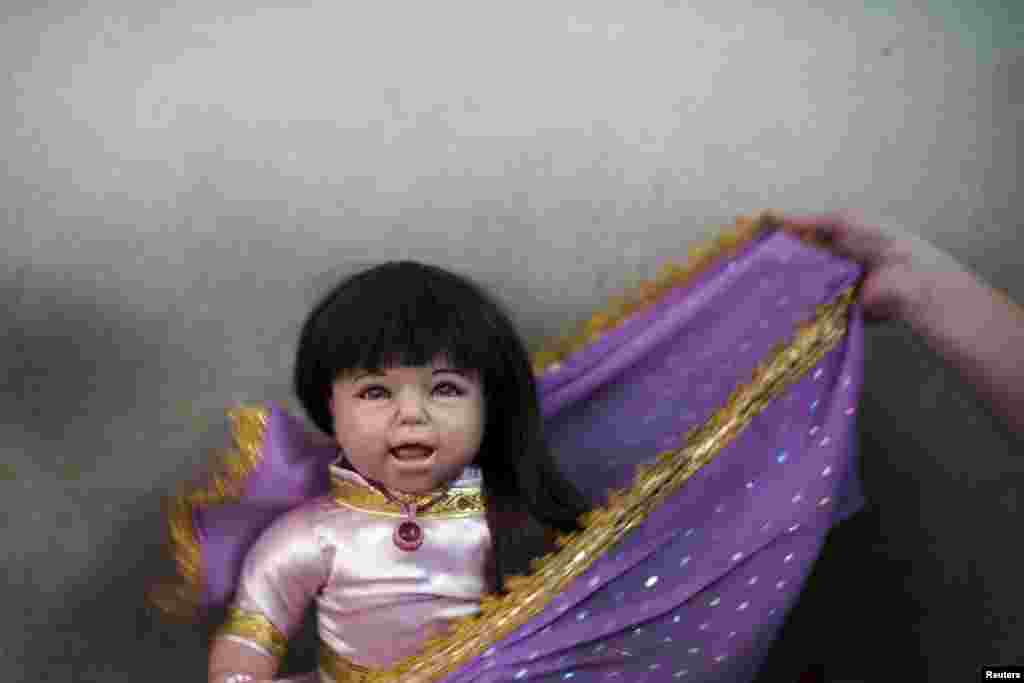 "A devotee dresses up her ""child angel"" doll near Wat Bua Khwan temple in Nonthaburi, Thailand, Jan. 26, 2016. A craze for lifelike dolls thought to bring good luck is sweeping Thailand, reflecting widespread anxiety as the economy struggles and political uncertainty persists nearly two years after a coup."