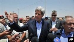 Menlu AS John Kerry didampingi Menlu Yordania Nasser Judeh (kanan), saat mengunjungi kemah pengungsi di Mafraq, Yordania (18/7). Menlu AS bertolak ke Tepi Barat untuk bertemu dengan Presiden Mahmoud Abbas dalam upaya lanjutan untuk menghidupkan kembali perundingan damai Palestina-Israel.