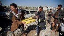 在也门,人们抬着死难者的尸体在废墟上走过。