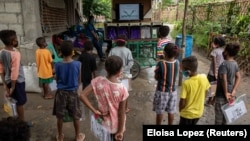 Aeta students watch instructional videos on the makeshift rickshaw for Aeta community distance learning amid the COVID-19 pandemic, in Porac, Pampanga, Philippines, October 12, 2020. (REUTERS/Eloisa Lopez)