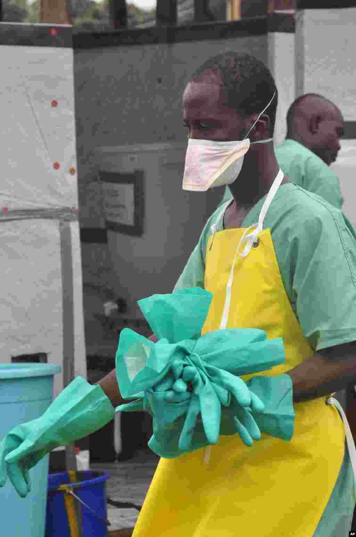 A health worker carries gloves at an Ebola treatment center, Monrovia, Liberia, Aug. 18, 2014.