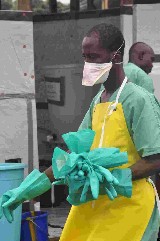 Un travailleur de la santé porte des gants à un centre de traitement d'Ebola dans la ville de Monrovia,