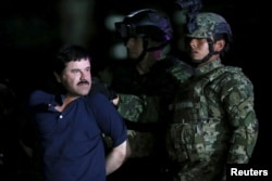 Joaquin 'El Chapo' Guzman is escorted by soldiers during a presentation at the hangar belonging to the office of the Attorney General in Mexico City, Mexico, Jan. 8, 2016.