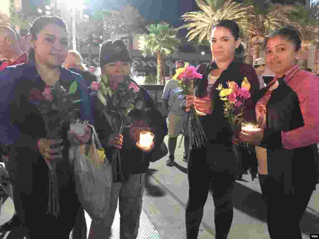 A group of women carry candles and flowers to vigil for victims of Las Vegas mass shooting, Oct. 2, 2017. (Photo: C. Mendoza / VOA)