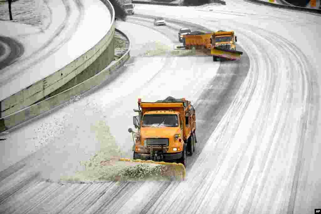 Varios limpa-neves a fazer o seu serviço na estrada Interstate 75/85 durante a tempestade de nebe em Atlanta, Georgia, Fev. 12, 2014.
