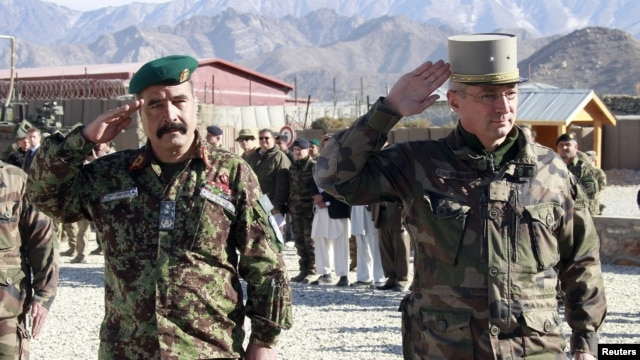 French General Eric Hautecloque Raysz (R) and his Afghan counterpart General Mohammad Zaman Waziri salute during handover ceremony, November 20, 2012.