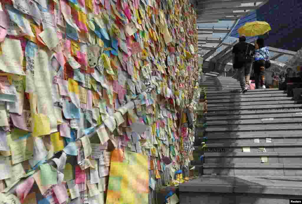 """Hàng ngàn những mẩu giấy ghi chú đầy màu sắc dán trên """"Lennon Wall"""" trong khi một đôi nam nữ cầm một cây dù màu vàng, biểu tượng của phong trào bất tuân dân sự Chiếm Trung, đi ngang qua tại địa điểm biểu tình Admiralty ở Hong Kong."""