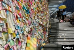 "Thousands of colourful notes are displayed on the ""Lennon Wall"" as a couple carrying a yellow umbrella, a symbol of the Occupy Central civil disobedience movement, walks past at the Admiralty protest site in Hong Kong, Nov. 17, 2014."