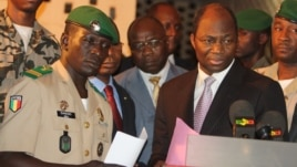 Coup leader Capt. Amadou Haya Sanogo, left, stands with Burkina Faso FM Djibrill Bassole, right, as they address the media at junta headquarters in Kati, outside Bamako, Mali, April 6, 2012.