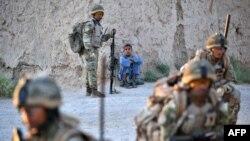 Soldiers from 1st Battalion the Royal Gurkha Rifles patrol through a village in Nahr e Saraj,