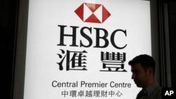 资料照:一名男子走过香港汇丰银行一个支行的广告灯箱。