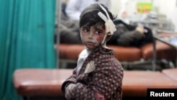 An injured boy waits inside a field hospital after what activists said were airstrikes and shelling by forces loyal to Syria's President Bashar al-Assad in the Douma neighborhood of Damascus, April 22, 2015.