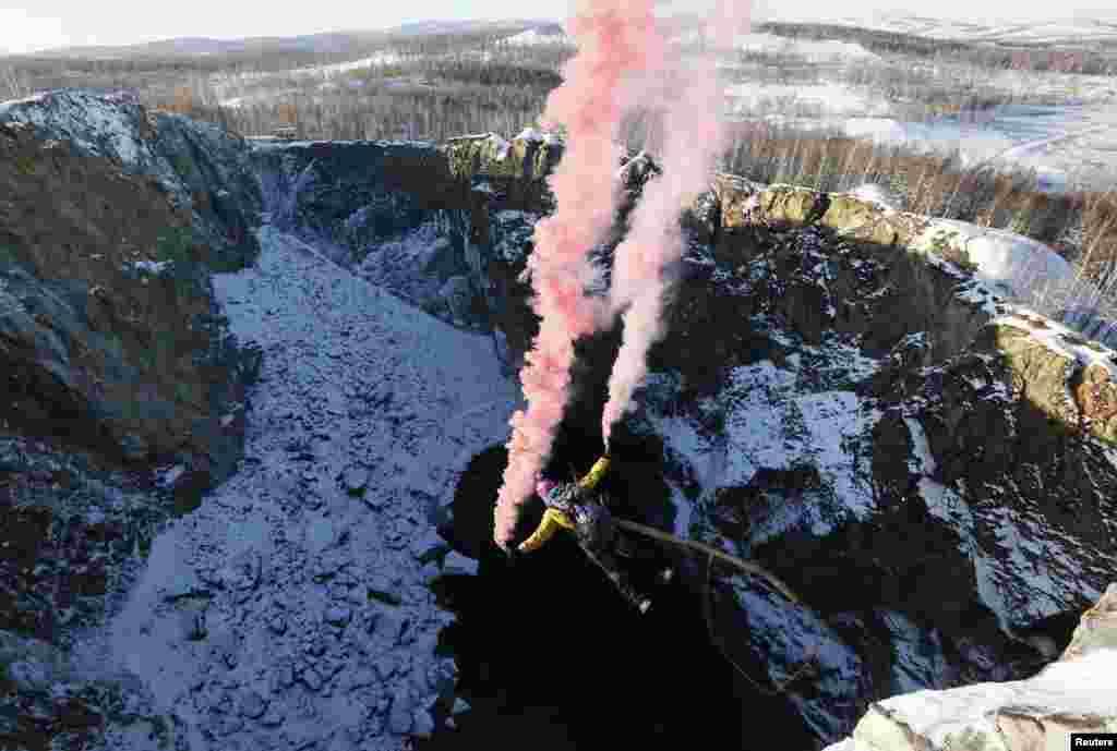 "Seorang atlet amatir melompat bungee (dengan diikat tali) dari ketinggian 120meterdi sebuah kawah buatan ""Tuimsky Proval"" di Siberia, Rusia."