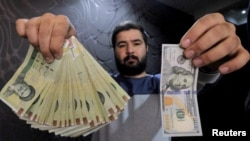 FILE - A money changer poses for the camera with a U.S hundred dollar bill (R) and the amount being given when converting it into Iranian rials (L), at a currency exchange shop in Tehran's business district, Iran, Jan. 20, 2016.