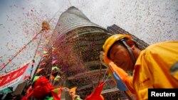 ຄົນງງານຜູ້ນຶ່ງເຂົ້າຮ່ວມພິທີເອົາເສົາຂຶ້ນຕິດຕັ້ງ ຢູ່ເທິງຈອມຕຶກ Shianghai Tower ໃນຂະນະທີ່ລົດຍົກໄດ້ຍົກເສົາສຸດທ້າຍ ຂຶ້ນໄປຕັ້ງໃສ່ຈອມຕຶກດັ່ງກ່າວ ທີ່ກໍາລັງກໍ່ສ້າງຢູ່ໃນເມືອງ Pudong ຊຶ່ງເປັນສູນກາງທາງການເງິນ ຢູ່ນະຄອນຊຽງໄຮໃນວັນທີ 3 ສິງຫາ 2013.