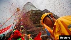 """随着最后一根钢梁星期六被起重机送上632米高的""""上海中心""""楼顶,工人参加庆祝仪式"""