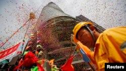"Seorang pekerja menghadiri perayaan ""Topping Out"" yang menandai pengangkatan tiang terakhir pembangunan menara Shanghai, gedung tertinggi kedua dunia di Pudong, Shanghai (3/8)."