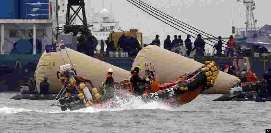 Searchers and divers look for people believed to have been trapped in the sunken ferry boat Sewol near the buoys marking the vessel in the water off the southern coast near Jindo, south of Seoul, South Korea.