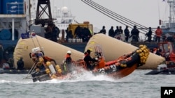 FILE - Searchers and divers look for people believed to have been trapped in the sunken ferry boat Sewol near the buoys which were installed to mark the vessel in the water off the southern coast near Jindo, south of Seoul, South Korea, April 22, 2014.
