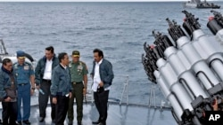 In this June 23, 2016 file photo released by the Indonesian Presidential Office, Indonesian President Joko Widodo, third right, accompanied by Indonesian officials on navy warship KRI Imam Bonjol, at the Natuna Islands, Indonesia.