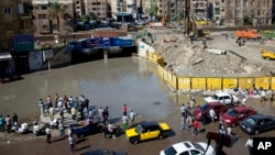 In this Oct. 25, 2015 file photo, Egyptians check floodwaters after a heavy rainfall in the coastal city of Alexandria, Egypt. (AP Photo/Heba Khamis, File)