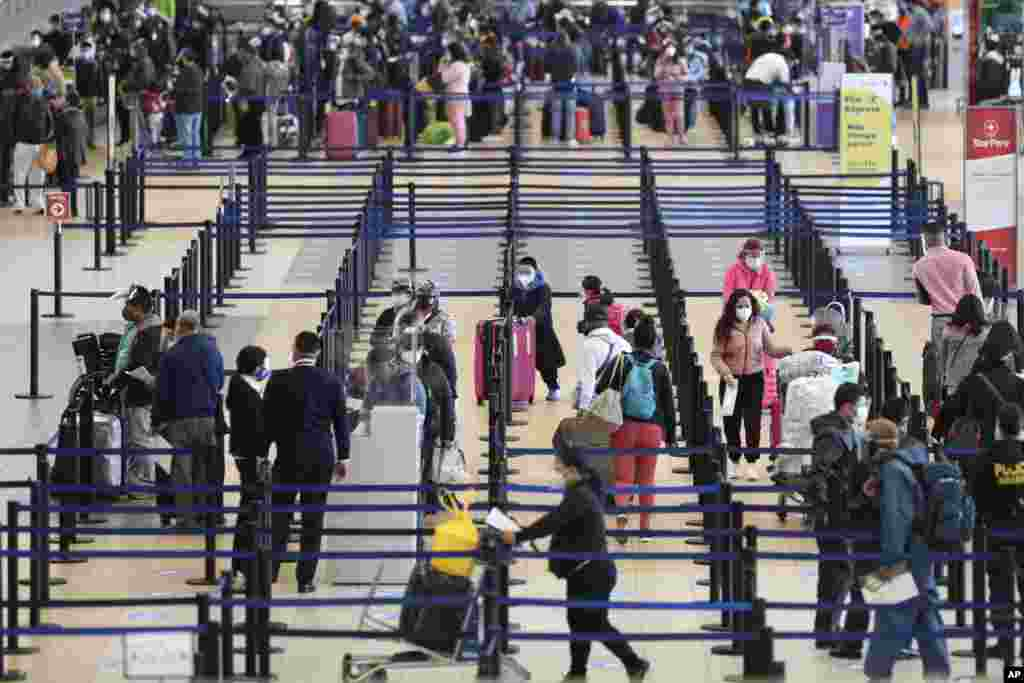 Passengers check-in at the Jorge Chavez International Airport in Callao, Peru, Monday, Oct. 5, 2020. After international flights were halted for more than six months amid the COVID-19 pandemic, Peru's largest airport resumed flights on Monday to Colombia, Ecuador, Panama, Paraguay, Uruguay, Bolivia, and Chile. (AP Photo/Martin Mejia)
