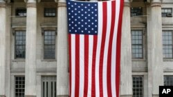 Two people sit on the steps of Brooklyn's Borough Hall where a huge American flag was displayed, Thursday, July 3, 2014.