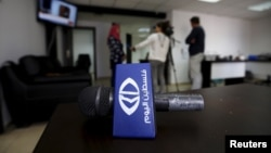 چھاپے کے بعد ٹیلی وژن اسٹیشن کے ملازمین سے صحافی انٹرویو لے رہے ہیں۔ 11 جنوری