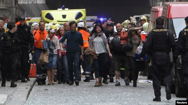 Injured people leave the area after an explosion in Prague, Apr. 29, 2013.