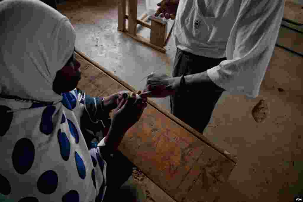 An IEBC official inks a voter's finger after he cast his ballot, March 4, 2013. (R. Gogineni/ VOA)